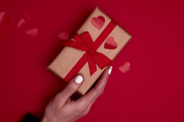 Composição de dia dos namorados com espaço de cópia. mão de uma mulher segurando uma caixa de presente ou presente embrulhada em papel artesanal com laço de fita e confete de corações vermelhos. close up, vista de cima, copie o espaço