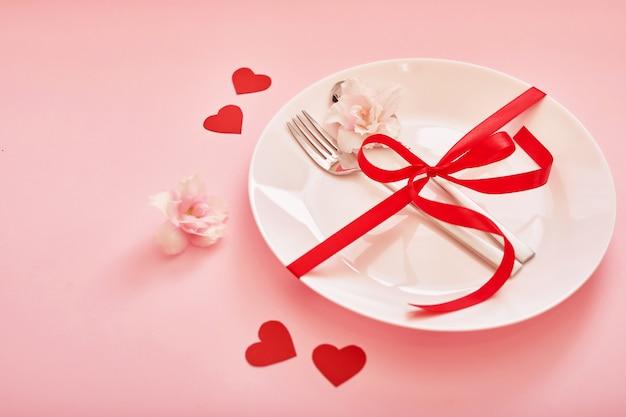 Composição de dia dos namorados com flores rosas vermelhas, prato e talheres.