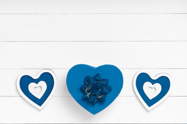 Composição de dia dos namorados. coração, presente na superfície de madeira branca. conceito de dia dos namorados. configuração plana