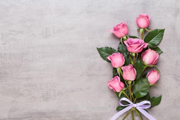 Composição de dia dos namorados de flores. moldura feita de rosa rosa em fundo cinza. camada plana, vista superior, espaço de cópia.