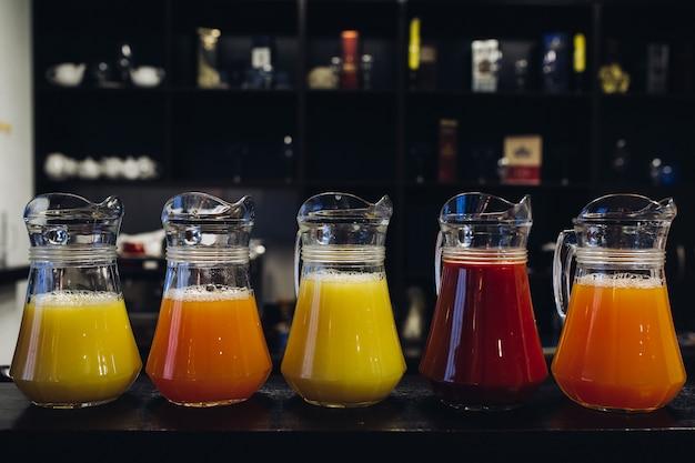 Composição de diferentes sucos saudáveis de frutas frescas em potes em jarras no bar