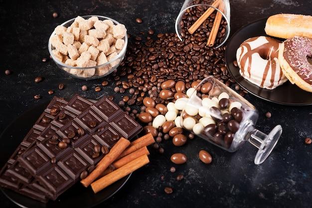 Composição de diferentes tipos de doces em fundo escuro de madeira