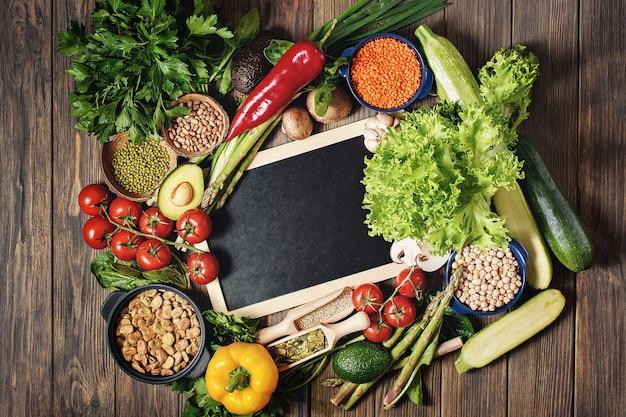 Composição de diferentes tipos de legumes em tigelas em fundo de madeira