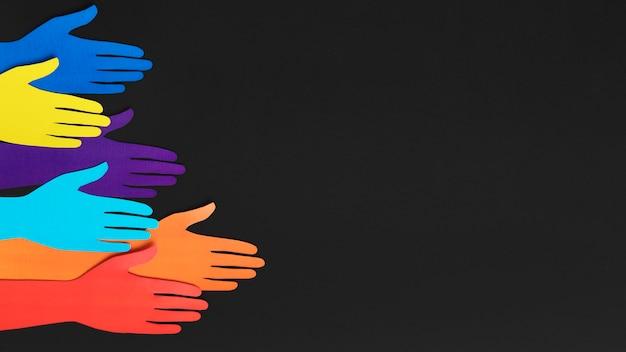 Composição de diversidade de vista superior com mãos de papel de cores diferentes com espaço de cópia