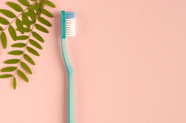 Composição de escovas de dentes coloridas em fundo rosa. postura plana.