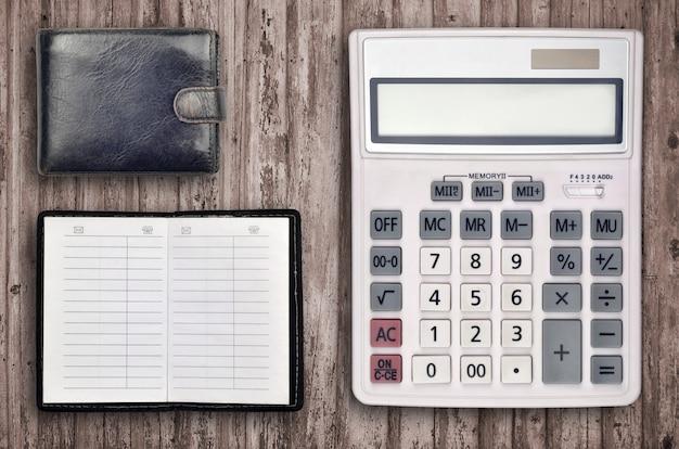 Composição de escritório com calculadora, livro de endereços e bolsa preta