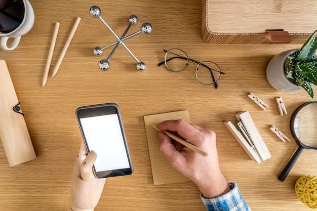 Composição de escritório em casa elegante de empresário que está usando simulação de tela do telefone, material de escritório, cactos, telefone, notas, plantas e acessórios pessoais no conceito de negócio plano leigo.