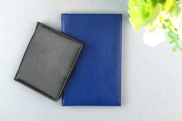 Composição de espaço de trabalho moderna e elegante com caderno de couro preto e azul na mesa com planta, foto de vista superior, espaço de cópia