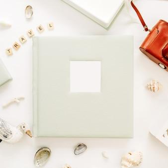 Composição de estilo de viagem com álbum de fotos, câmera retro, escultura de pássaro na superfície branca