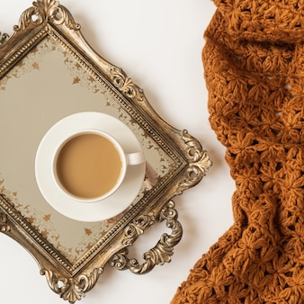 Composição de estilo de vida com uma xícara de café com leite na bandeja dourada vintage e manta de manta marrom de malha em fundo branco. postura plana