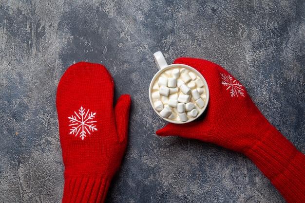 Composição de férias aconchegante de natal e ano novo com cachecol, mãos de mulher em luvas, canecas com bebida quente e marshmallow no fundo cinza de concreto. vista plana leiga, superior.