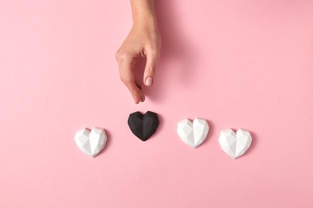 Composição de férias com corações de gesso cores brancas e um preto e mão de mulher