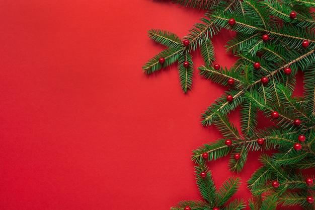 Composição de férias de ano novo de natal. galhos de pinheiro com bagas em vermelho