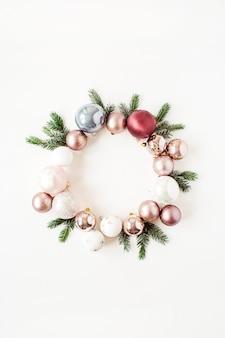 Composição de férias de ano novo de natal. grinalda de moldura com espaço de cópia simulado de bolas de enfeites de natal e galhos de pinheiro em branco