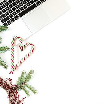 Composição de férias de ano novo de natal. mesa de escritório em casa com laptop, bolas de enfeites de natal, galhos de pinheiro, palitos de chocolate em branco