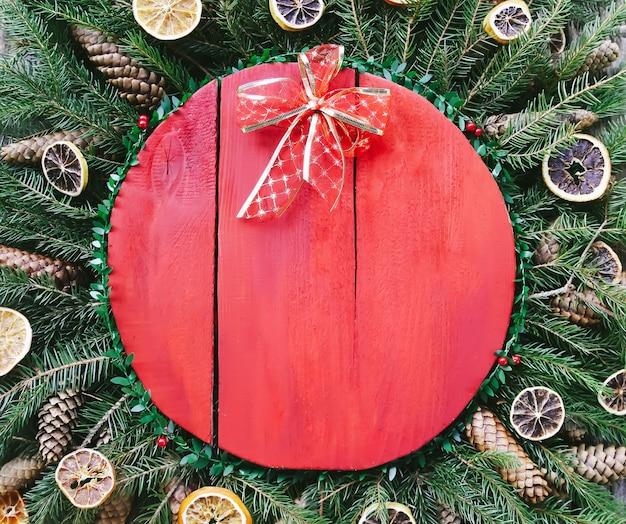 Composição de férias de inverno de natal e ano novo com superfície de madeira vermelha em galhos de árvore verde do abeto, fatias de laranja secas, cones, caixa de presente e laço vermelho.