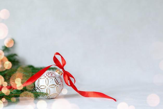 Composição de férias de natal com bola branca e fita vermelha em fundo claro