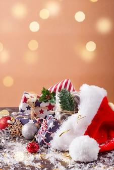 Composição de férias de natal com chapéu vermelho de papai noel e caixas de presente em fundo de madeira.
