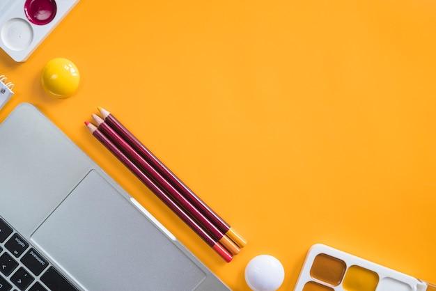 Composição de ferramentas de laptop e papelaria para pintura