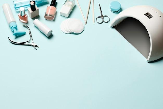 Composição de ferramentas de manicure e cosméticos, esmaltes, lâmpada para manicure, lâmpada uv sobre um fundo azul. lugar para texto.