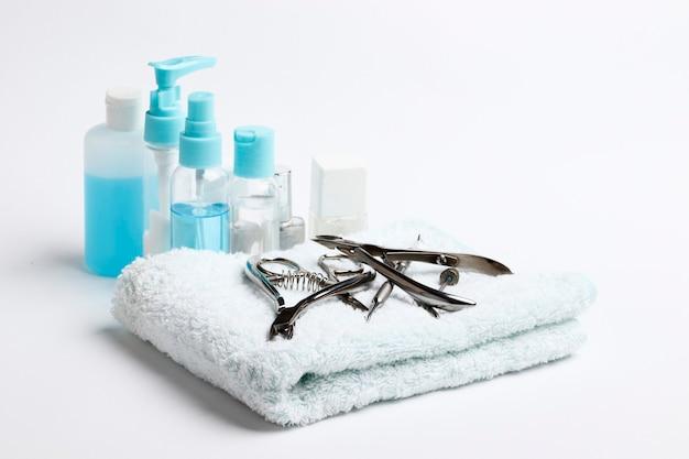 Composição de ferramentas de manicure, potes de cosméticos em um fundo branco
