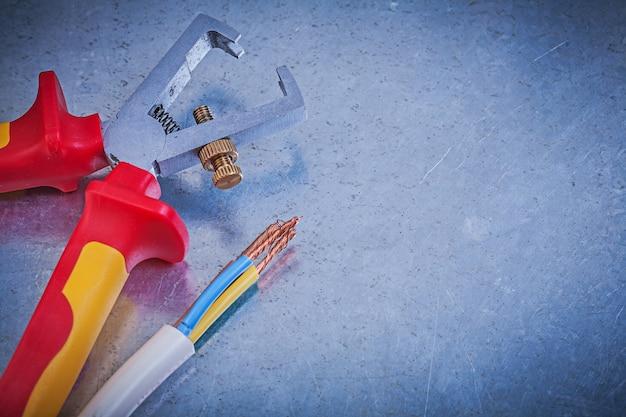 Composição de fios elétricos de decapantes de isolamento na mesa metálica, conceito de eletricidade