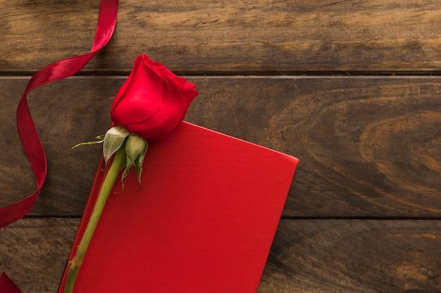 Composição de flor vermelha perto de fita e papel