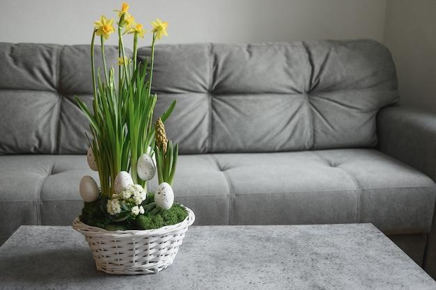 Composição de flores amarelas da páscoa no interior da casa com sofá cinza na sala de estar