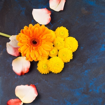 Composição de flores amarelas e pétalas de rosa