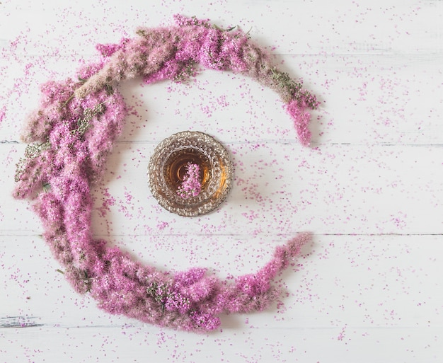 Composição de flores. círculo feito de flores cor de rosa com um copo de chá branco