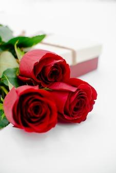 Composição de flores com caixa de presente forma de coração feita de flores rosa