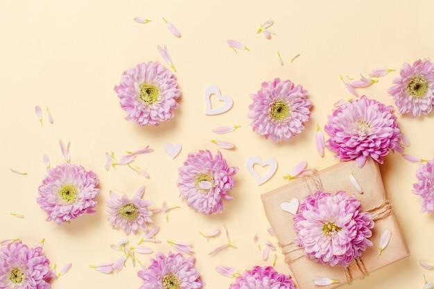 Composição de flores com corações e caixa de presente em um fundo amarelo pastel