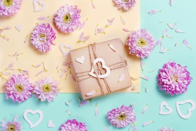 Composição de flores com corações e caixa de presente em um fundo rosa pastel