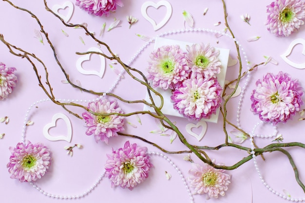 Composição de flores com corações em um fundo rosa pastel