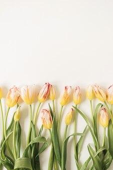 Composição de flores com muitas tulipas amarelas em branco
