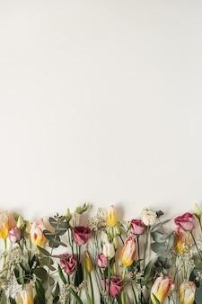 Composição de flores com muitas tulipas, eucaliptos, flores silvestres em branco