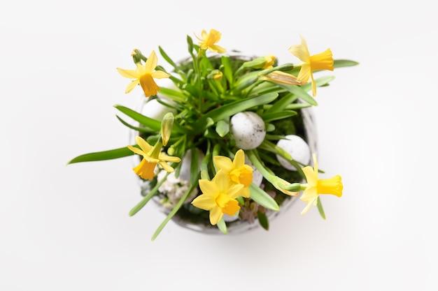 Composição de flores de páscoa com jacinto de narciso e ovos festivos em uma cesta de vime em branco