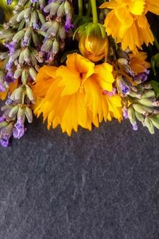 Composição de flores do campo. quadro feito de várias flores coloridas em fundo escuro. vista plana, vista superior, cópia espaço, composição vertical
