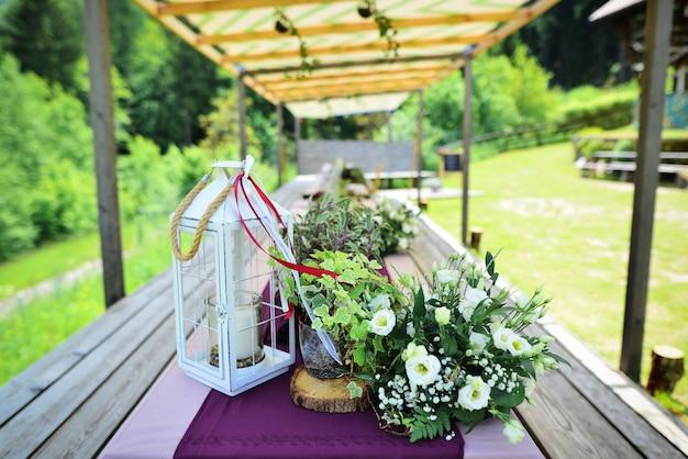 Composição de flores e folhagens em pé na mesa servida na área da festa de casamento