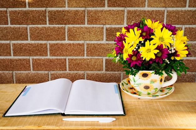 Composição de flores em uma caneca de chá e um caderno sobre uma mesa de madeira pela manhã no verão ou primavera.