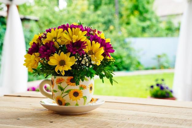 Composição de flores em uma caneca de chá em uma mesa de madeira de manhã no verão ou na primavera.