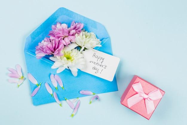 Composição de flores frescas com tag no envelope perto do presente