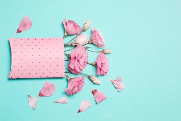 Composição de flores frescas e bonitas em pacote de papel perto de pétalas