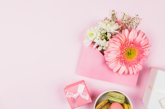 Composição de flores frescas no envelope perto de presente e macaroons
