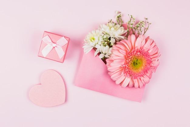 Composição de flores frescas no envelope perto do coração presente e ornamental