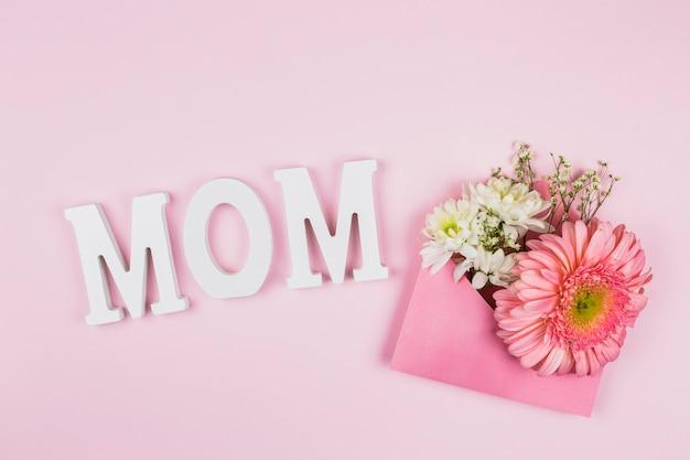 Composição de flores frescas no envelope perto do título da mãe