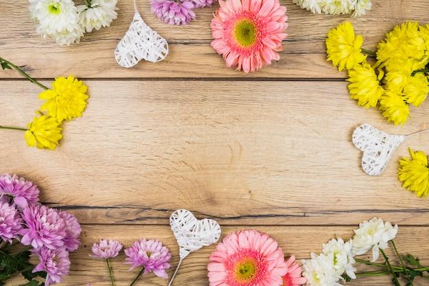 Composição de flores frescas perto de corações ornamentais em varinhas