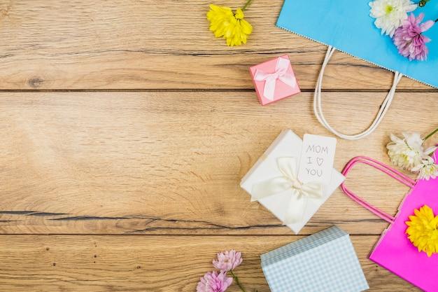 Composição de flores frescas perto de tag em caixas de presentes perto de pacotes de papel