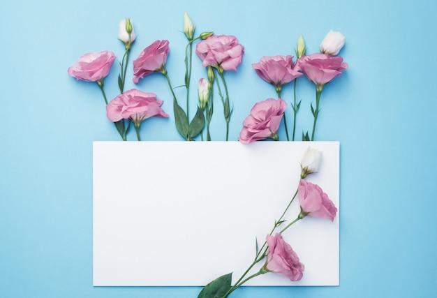 Composição de flores. grinalda feita de flores cor de rosa com cartão de papel branco sobre fundo azul.