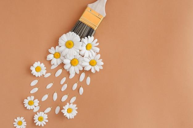 Composição de flores. layout criativo feito de flores de camomila brancas e pincel em fundo pastel. camada plana, vista superior, espaço de cópia.